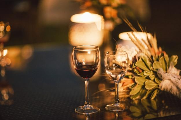 Zwei gläser wein auf tabelle auf dem hintergrund des hochzeitsblumenstraußes, glättend, ende des ereignisses