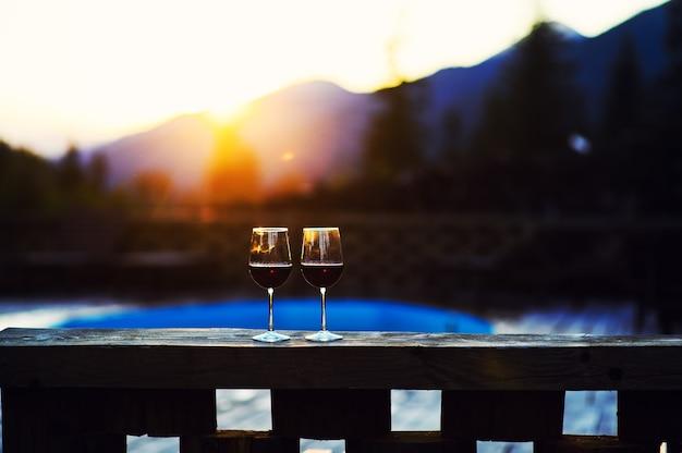 Zwei gläser wein bei sonnenuntergang dramatischen himmel auf berglandschaft hintergrund