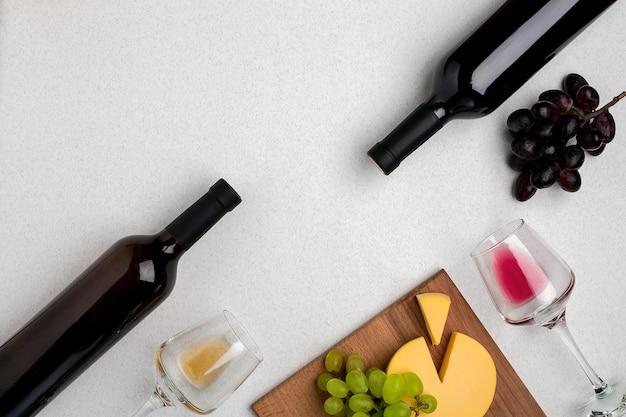 Zwei gläser weiß- und rotweinkäse und trauben draufsicht