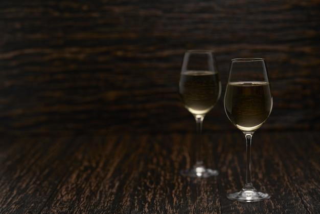 Zwei gläser weißwein auf einem schwarzen holztisch, mit kopienraum.