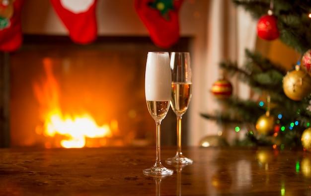 Zwei gläser werden mit champagner auf dem tisch neben dem weihnachtsbaum gefüllt