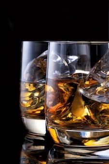 Zwei gläser whisky auf dem tisch mit einer flasche