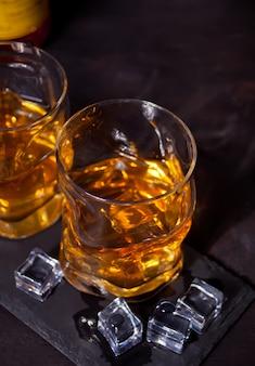Zwei gläser whisky mit eis auf einem schwarzen tisch.