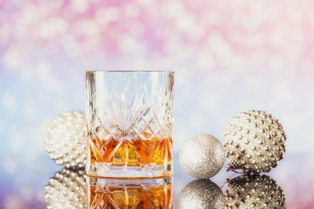 Zwei gläser whisky oder bourbon mit weihnachtsdekoration auf einem hellen bokeh-hintergrund. whisky-stimmungskonzept für neujahr, weihnachten und winterferien