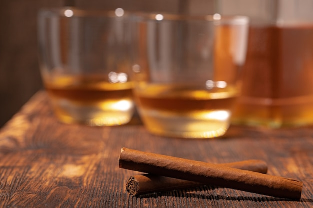Zwei gläser whisky und zigarren auf holztisch schließen oben
