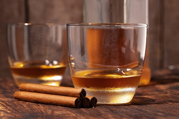 Zwei gläser whisky und zigarren auf holztisch