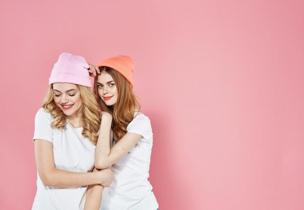 Zwei glamouröse freundinnen in t-shirts bunte hüte kommunizieren rosa wand.