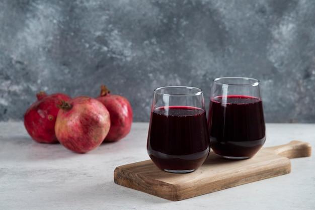 Zwei glas eines roten granatapfels, der saft auf holzbrett trinkt.