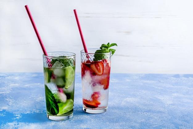 Zwei glas erfrischendes kühles getränk mit erdbeere, limette und minze auf blauem tisch. verschiedene sommerlimonaden oder eistee. mojito-cocktail mit eiswürfeln.