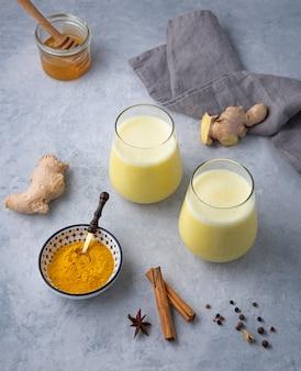 Zwei glas goldene milch mit kurkuma-gewürz und honig auf blauem hintergrund