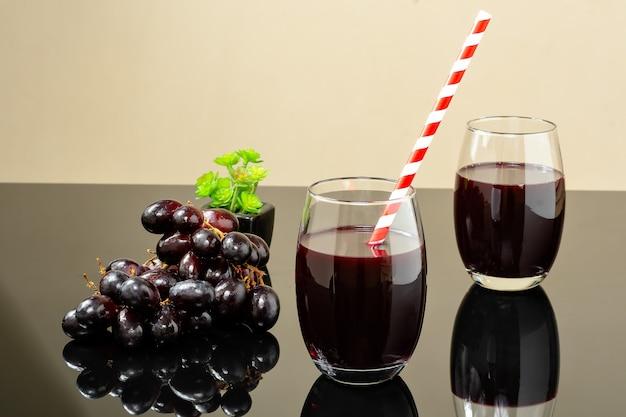 Zwei glas voll traubensaft auf einem reflektierenden fuss mit einem traubenruf neben dem glas
