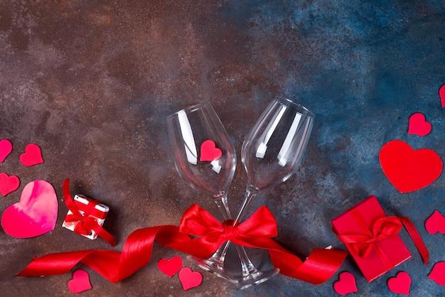 Zwei glas wein, herzen und geschenkbox auf steinhintergrund. valentinstag
