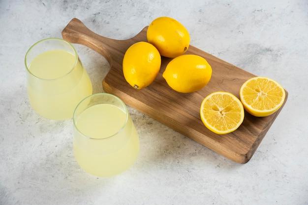 Zwei glasbecher frische limonade auf einem holzbrett.