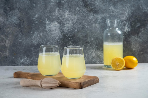 Zwei glasbecher limonade auf einem holzbrett.