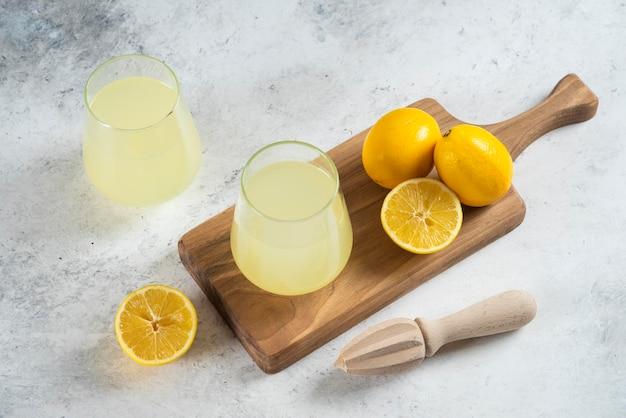 Zwei glasbecher limonade und holzreibahle.