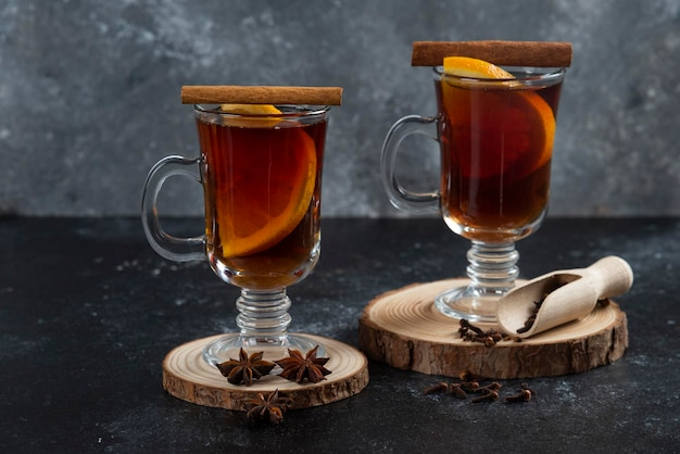 Zwei glasbecher mit frischem tee und zimtstangen.