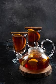 Zwei glasbecher mit heißem tee und zimtstangen.