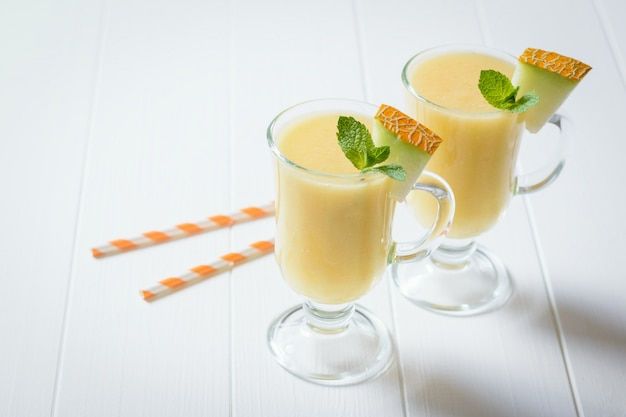 Zwei glasbecher mit melonen-smoothie auf einem weißen holztisch.