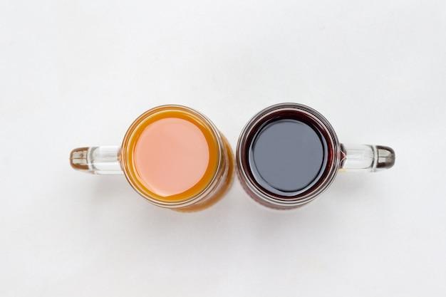 Zwei glasbecher mit orangen- und burgundergetränken. weißer hintergrund. flach liegen. abstraktes bild