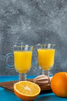 Zwei glasbecher orangensaft auf holzbrett.