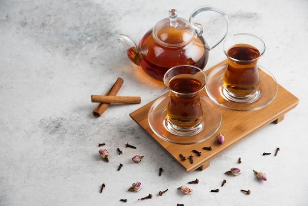Zwei glasbecher tee mit zimtstangen und getrockneten rosen.