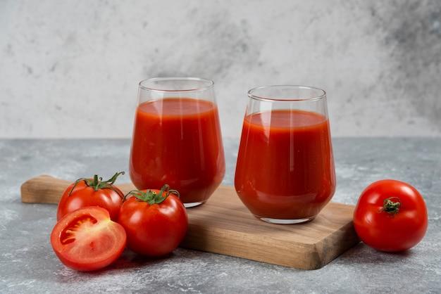 Zwei glasbecher tomatensaft auf einem holzbrett.