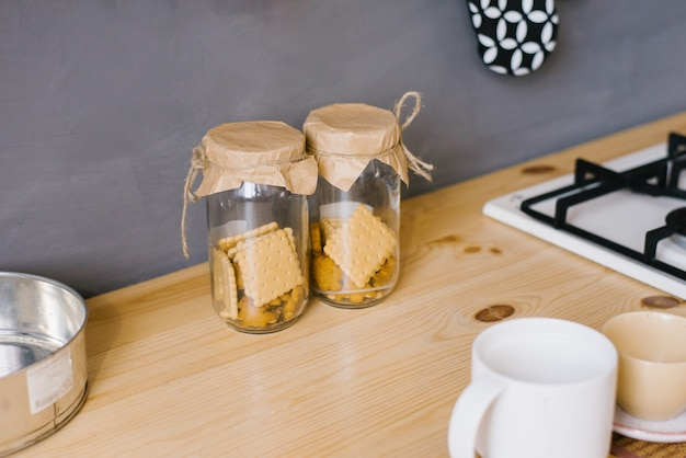 Zwei glasgefäße selbst gemachte plätzchen auf einer hölzernen arbeitsplatte in der küche