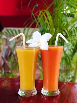 Zwei glasgläser mit frisch gepresstem saft und frangipani-blume