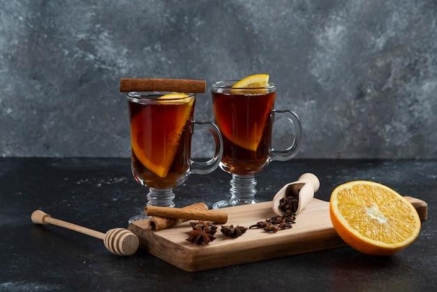 Zwei glastassen tee und mit zimtstangen und holzschöpflöffel.