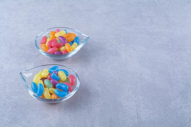 Zwei glasteller mit fruchtsüßen bohnenbonbons auf blaugrauer oberfläche