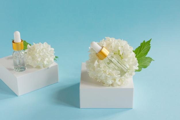 Zwei glastropfflaschen für medizinische und kosmetische zwecke und weiße zarte blüten auf hellblauem hintergrund. hautpflege- und spa-konzept.