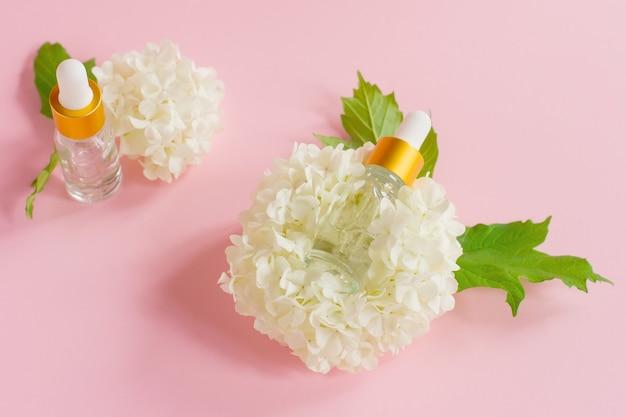 Zwei glastropfflaschen für medizinische und kosmetische zwecke und weiße zarte blüten auf hellrosa hintergrund. hautpflege- und spa-konzept.