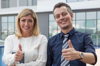 Zwei glückliche männliche und weibliche Geschäftsleute, die sich Daumen draußen zeigen.