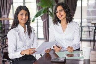 Zwei glückliche weibliche Kollegen, die mit Dokumenten im Café arbeiten.