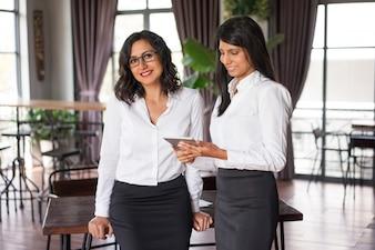 Zwei glückliche weibliche Kollegen, die Tabletten-PC im Café verwenden.