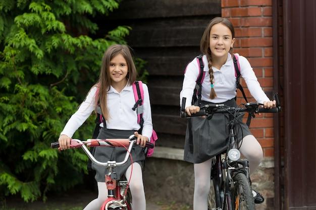 Zwei glücklich lächelnde mädchen in uniform, die mit dem fahrrad zur schule fahren