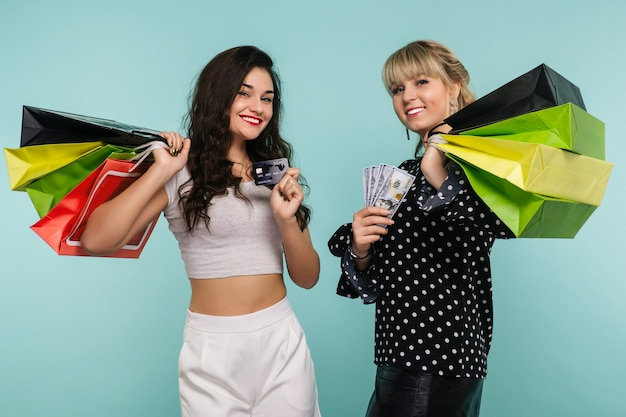 Zwei glücklich lächelnde mädchen mit einer kreditkarte und einem bündel dollar stehen mit einkaufstüten in ihren händen auf einem blau