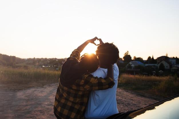 Zwei glückliche afroamerikanische frauen in der nähe des autos schauen auf den sonnenuntergang, lifestyle