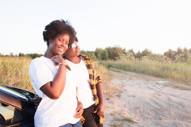 Zwei glückliche afroamerikanische frauen nahe dem auto bei sonnenuntergang, lebensstil.