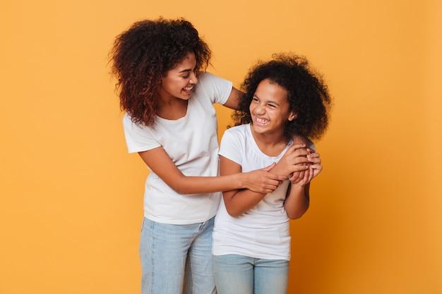 Zwei glückliche afroe-amerikanisch schwestern, die spaß bei der stellung haben