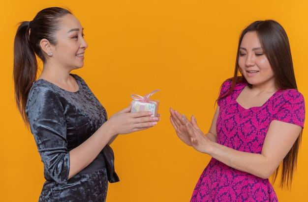 Zwei glückliche asiatische frauen feiern den internationalen frauentag glückliche frau, die ihrem ablehnenden freund ein geschenk gibt, das über orange wand steht