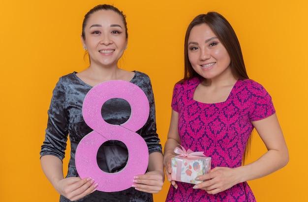 Zwei glückliche asiatische frauen feiern den internationalen frauentag mit der nummer acht