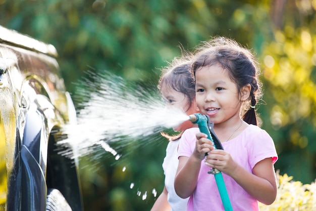 Zwei glückliche asiatische kindermädchen, die spaß haben, elternwaschauto zusammen mit sonnenlicht zu helfen