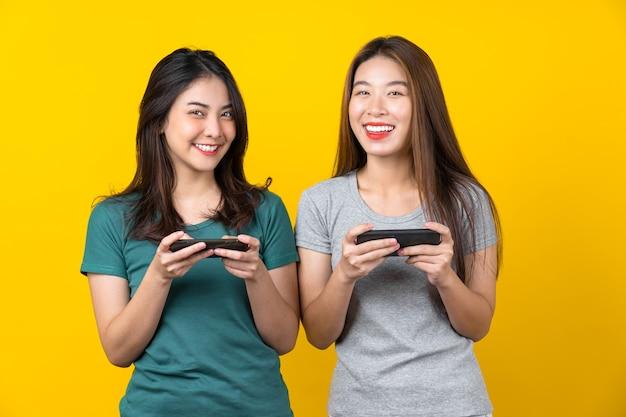 Zwei glückliche asiatische lächelnde junge spielerin, die intelligentes mobiltelefon verwendet