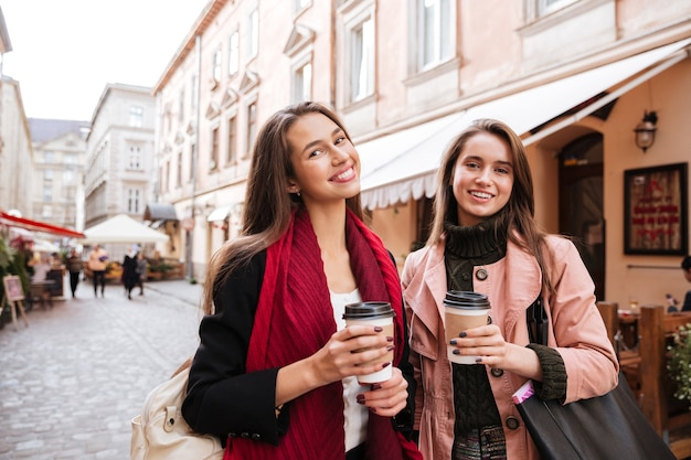 Zwei glückliche attraktive junge frauen mit kaffee zum spazierengehen und reden in der altstadt