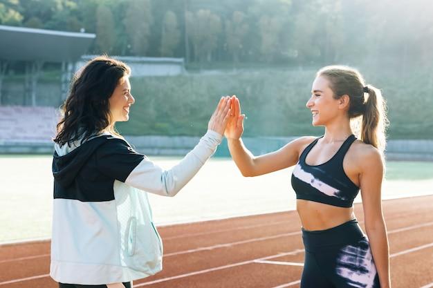 Zwei glückliche attraktive junge sportlerinnen, die nach dem training der entspannenden sportlerinnen high five geben