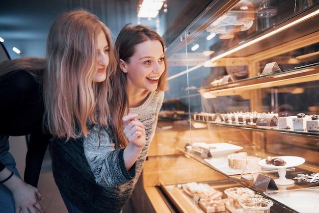Zwei glückliche attraktive mädchen, die köstliche ganachen, praline und schokoladen wählen