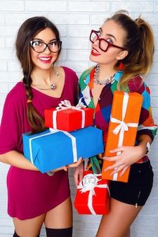 Zwei glückliche beste freunde, die helle geschenke und geschenke halten