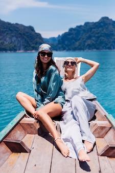 Zwei glückliche blogger-touristenfreunde in seidenanzug und schal und sonnenbrille im urlaub reisen um thailand auf asiatischem boot, khao sok nationalpark.
