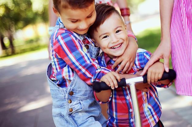 Zwei glückliche brüder, die spaß zusammen im park haben. kleine jungs